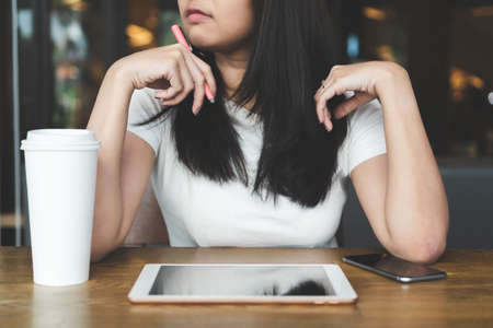 Young asian business woman in smart casual working and thinking about new startup project with tablet laptop, smartphone and coffee on wooden desk in modern office or cafe.