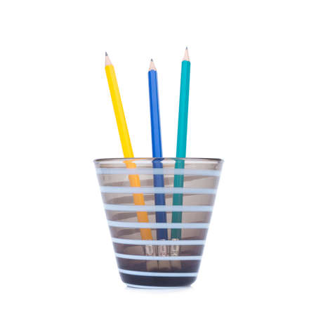 Pencils green blue yellow in the pencil holders on white background
