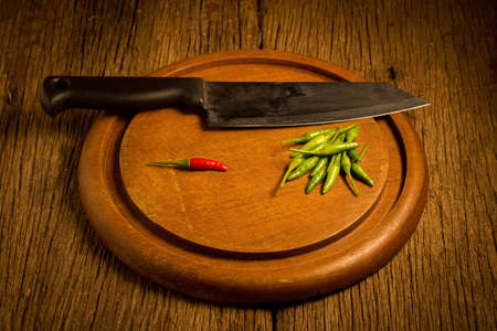 Round wood Chopping cutting board. chili peppers green and red. knife. Stok Fotoğraf