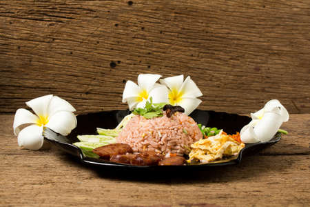 Kao Klook Ga-pi (Rice Mixed with Shrimp paste) on old wood.