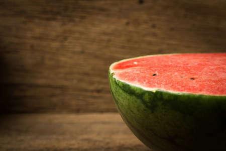 Half of ripe watermelon on old wood.