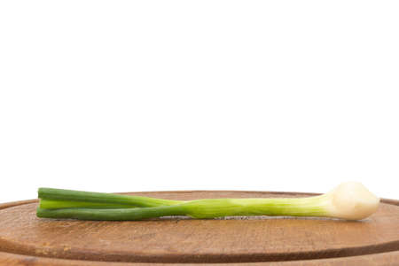 Spring onion on chopping board isolated on white background.