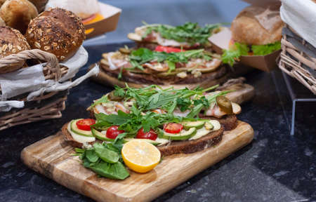 Sandwiches with tomatoes, lettuce, ham, lemon and arugula on dark bread.