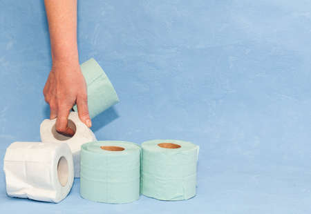 4 rolls of soft toilet paper in hand with space for text. Covid-19 pandemic. Increased potential. High unexpected demand. Deficit.