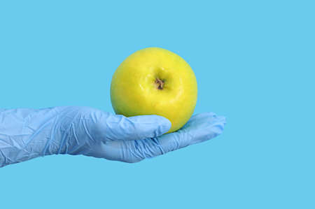 Using gloves when people buy in a shop or market during coronavirus. Hand in latex gloves holding fruit