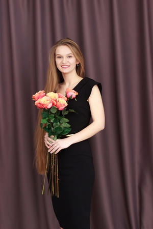 Pretty blonde girl holding a bunch of colouful flowers in her hands