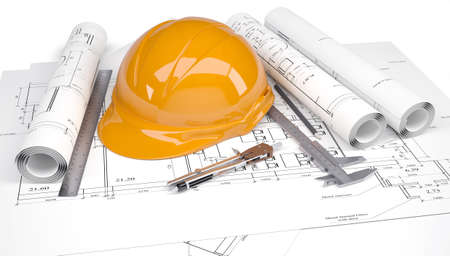 Orange construction helmet on the architectural drawings with engineering tools