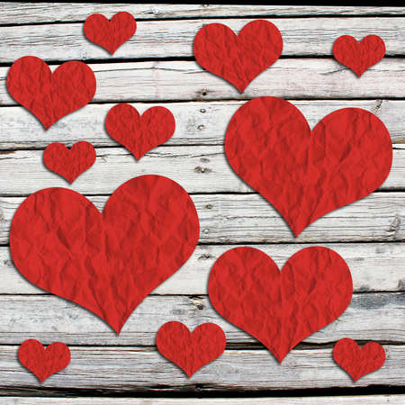 Paper hearts on a wooden surface  The concept of Valentine s Day photo