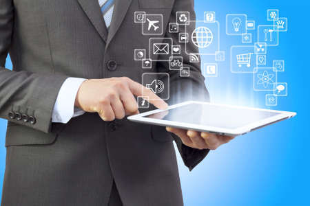 Businessman in a suit holding a tablet computer  Application icons are emitted from the tablet photo
