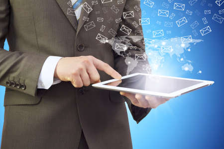 Businessman in a suit holding a tablet computer  Letters icons fly out of the tablet photo
