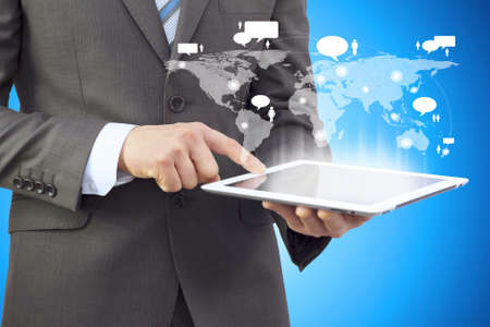 Businessman in a suit holding a tablet computer  The screen tablet - contacts and world map photo