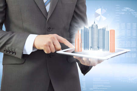 Businessman in a suit holding a tablet computer  On the screen of the tablet are skyscrapers photo