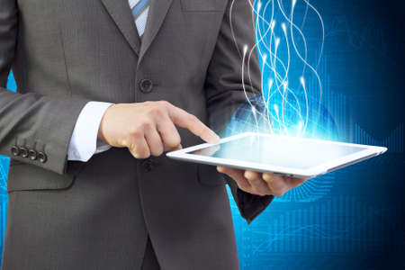Businessman in a suit holding a tablet computer  Rays emitted from the tablet photo