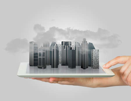 Hands holding a tablet computer  In screen tablet city of skyscrapers and smoke photo