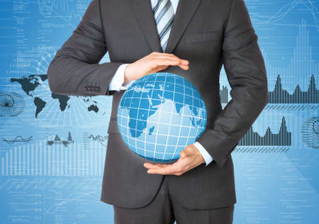 Businessman in a suit holding a globe  Graphs and figures on background photo
