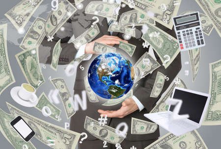 Businessman in a suit holding a earth  Money falling around   photo