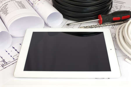 Electrical cable and tablet pc on the construction drawings  Repair and construction of electric systems photo