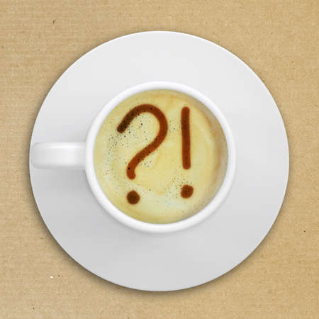 crema: Cup of coffee standing on a cardboard surface  Picture of the question and exclamation marks in the coffee crema  top view Stock Photo
