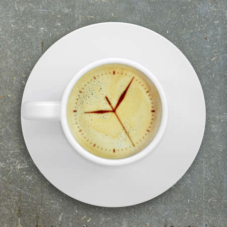 Cup of coffee standing on a abstract surface  Picture of the clock face in the coffee crema  top view photo