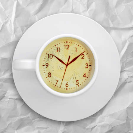 crema: Cup of coffee standing on a crumpled paper  Picture of the clock face in the coffee crema  top view