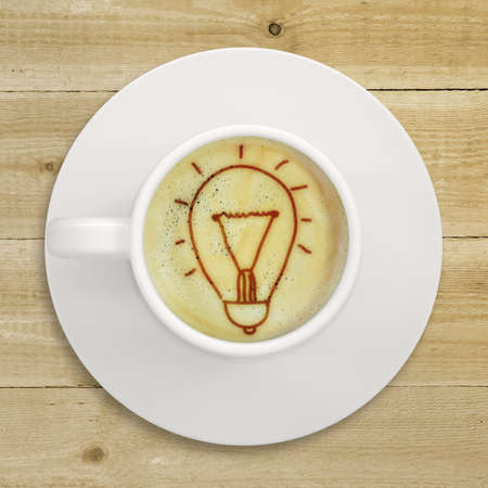 crema: Cup of coffee standing on a wooden surface  Picture of the light bulb in the coffee crema  top view
