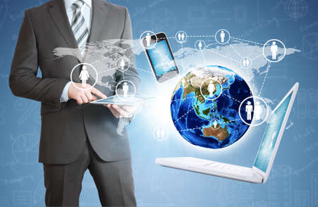 Businessman in a suit holding a tablet  Near the earth and electronics  Elements of this image are furnished by NASA photo
