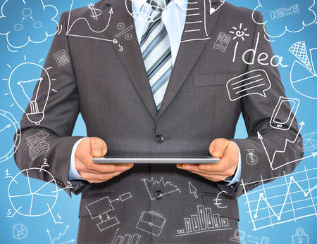 Businessman with a tablet in hands and business sketches  Business concept photo