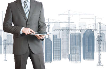 Businessman in suit hold tablet pc  Wire frame tower crane and skyscrapers on the background photo