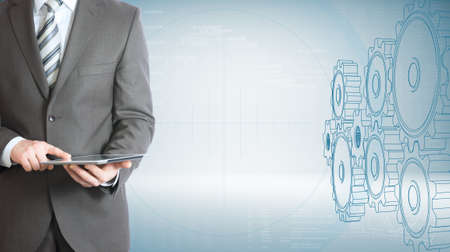 hold high: Businessman hold tablet pc  High-tech wire frame gears and graphs at backdrop Stock Photo