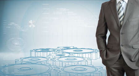 Businessman standing with hands in pockets  High-tech wire frame gears and graphs at backdrop photo