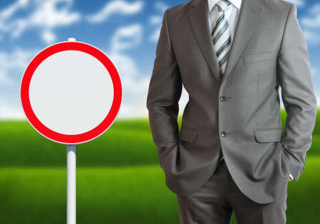 Businessman with road sign  Blue sky and green grass as backdrop photo