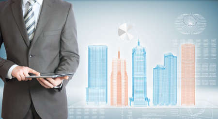 Businessman holding tablet pc  On background of the high-tech wire frame skyscrapers and graphs photo