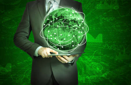 Businessman holding tablet in his hands  Glowing graphs and Earth  Elements of this image are furnished  photo