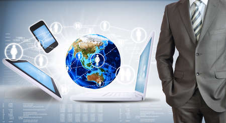 Businessman with the earth and electronics  High-tech graphs at backdrop  Elements of this image photo