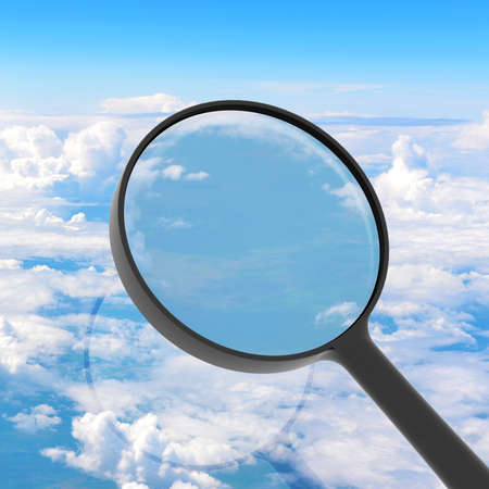 Magnifying glass looking sky in background  View from above the clouds photo