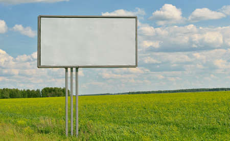 Large empty billboard on a background of grass, forest and blue sky photo