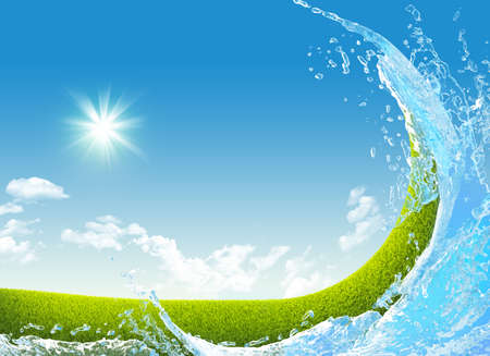Green meadow and water splash on blue sky background photo