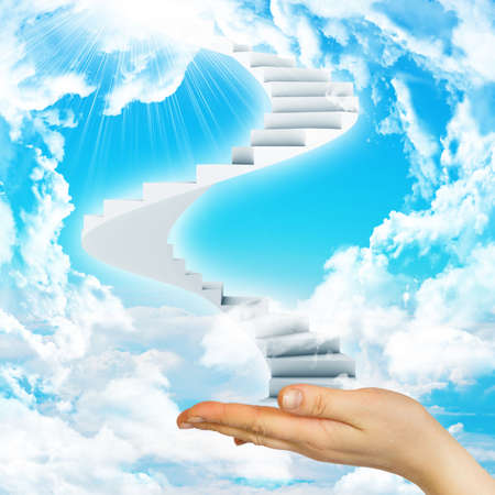 Hand hold spiral stairs in sky with clouds and sun. Concept background photo