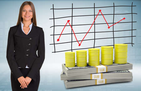 Businesswoman with barrels gas and money photo