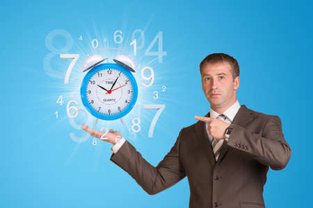Businessman hold alarm clock with figures photo