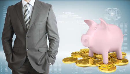 Businessman with piggy bank and gold coins photo