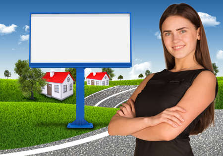 Businesswoman with empty billboard, trees and houses  photo
