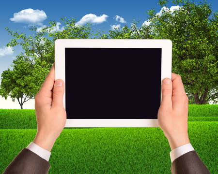 Digital tablet in hands with grass field and trees as backdrop photo