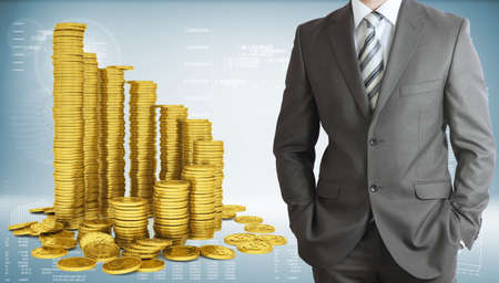 Businessman with pyramid of gold coins photo