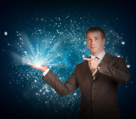 Business man hold magic light in hand photo