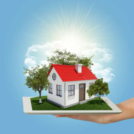 tablet pc in hand: Human hand holding tablet pc with small house and trees Stock Photo