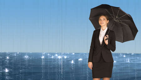 Businesswoman holding umbrella photo