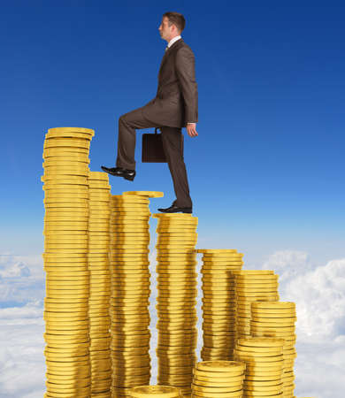 Businessman climbing stairs of gold coins photo