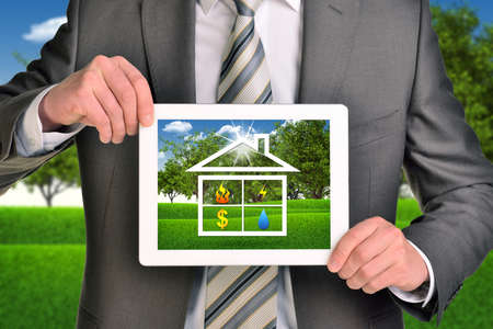 Two hands holding tablet pc with picture of house icon  photo