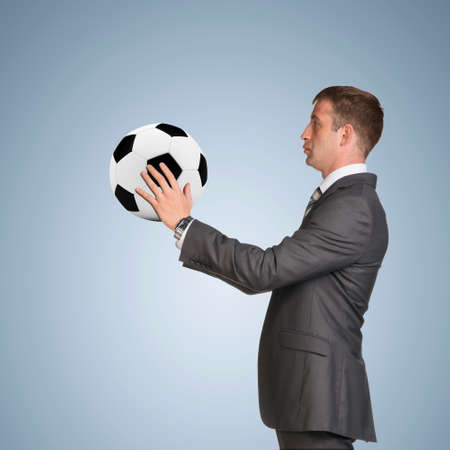half turn: Businessman in suit hold soccer ball